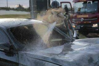 Motorista de BMW passa por cima de canteiro, bate em poste e carro pega fogo